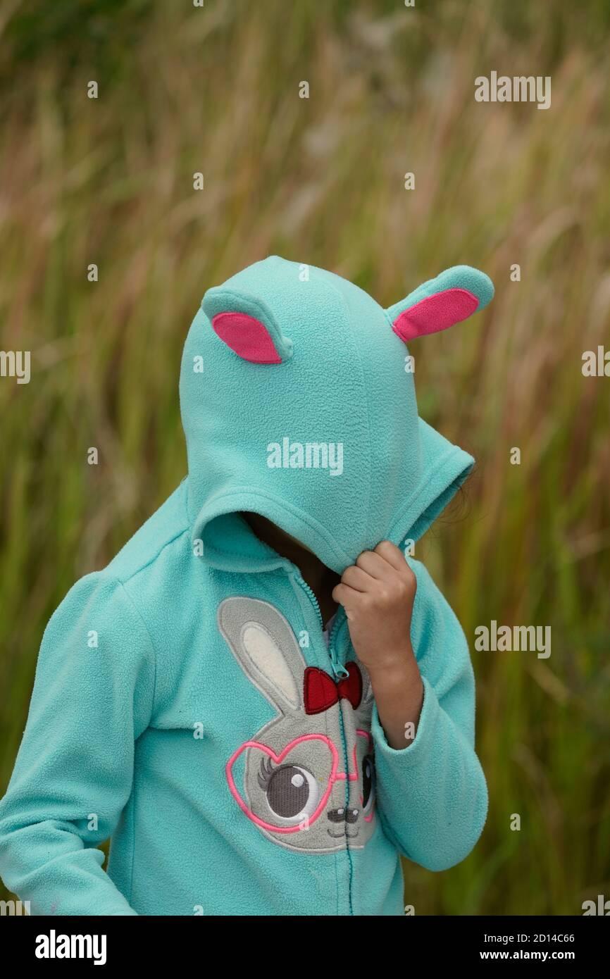 Chica que se esconde detrás de una sudadera con capucha de conejo Foto de stock