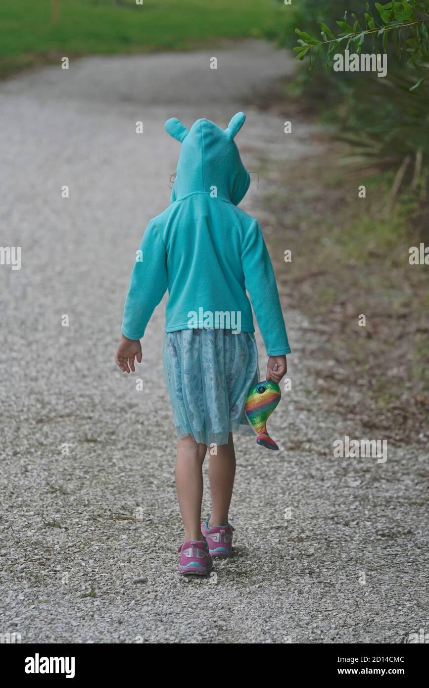 Una chica que lleva una sudadera con capucha de conejo camina por un camino Foto de stock