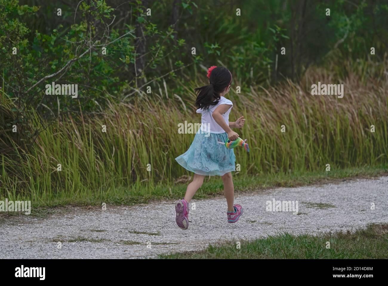 Niña de cinco años corriendo en un sendero. Foto de stock