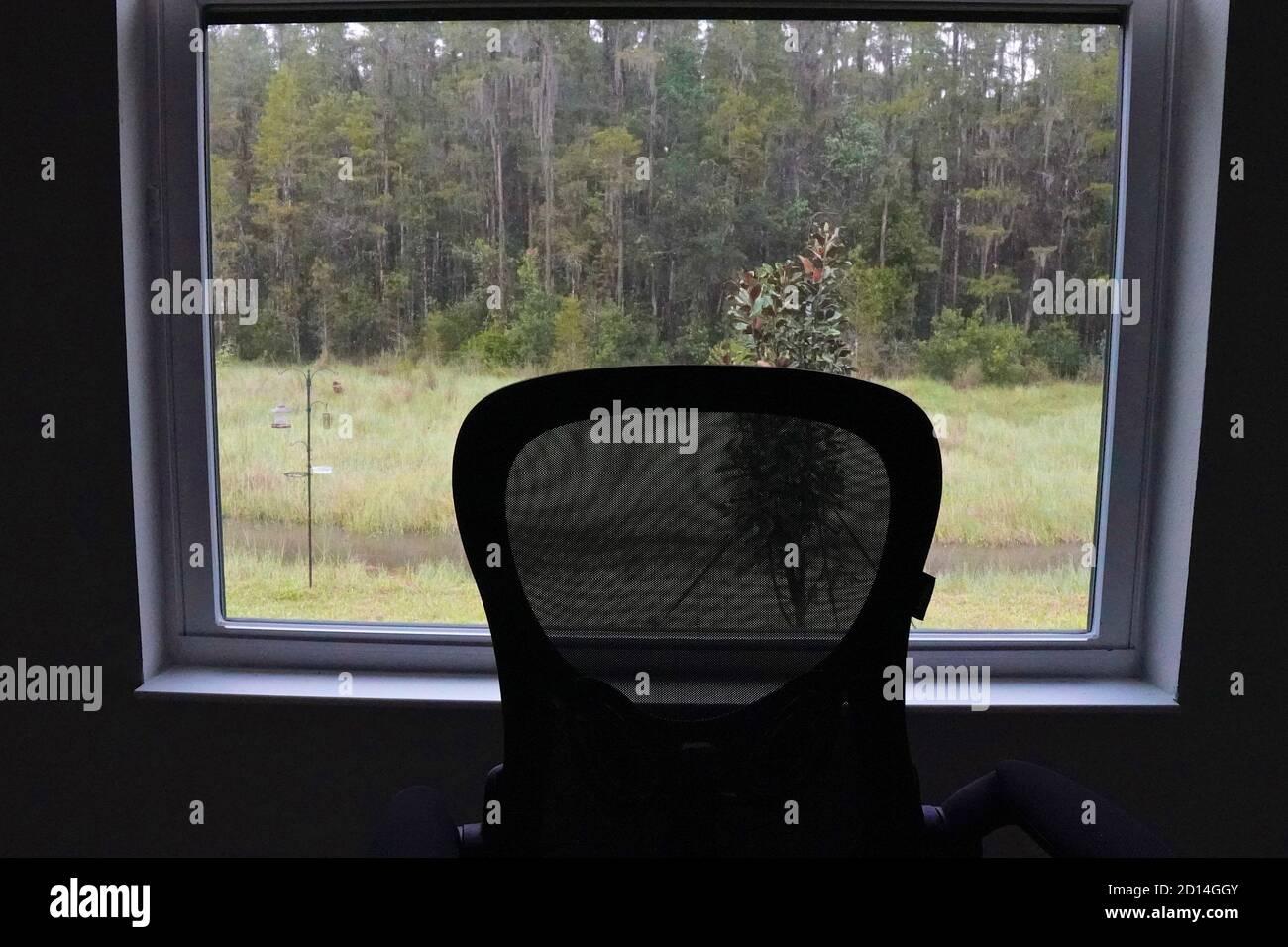 Silla vacía frente a una ventana con vistas a un bosque Foto de stock