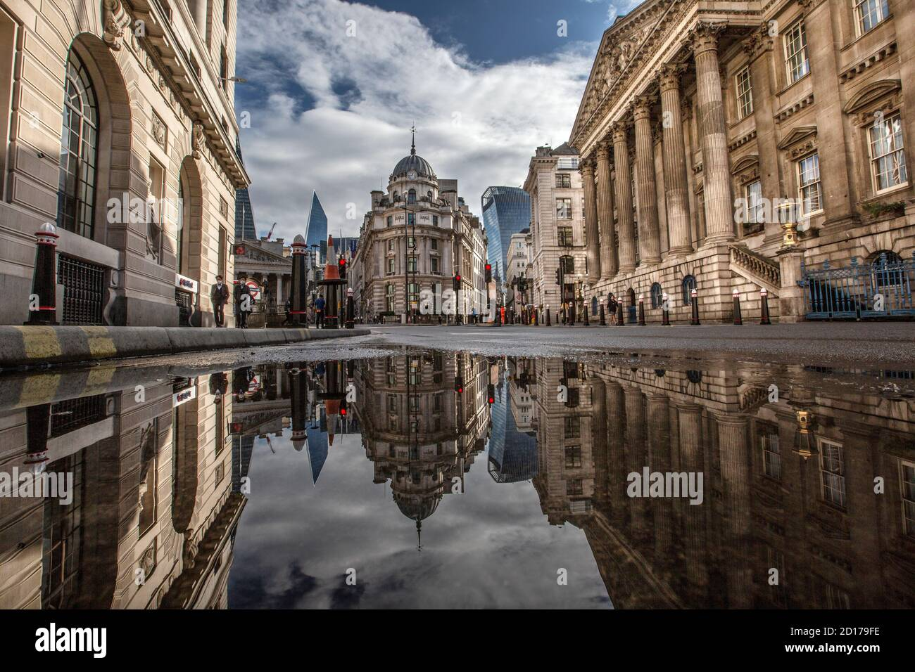 Bank of England y Royal Exchange en el corazón del distrito financiero de la ciudad de Londres reflejado en un charco en Threadneedle Street, Londres. Foto de stock