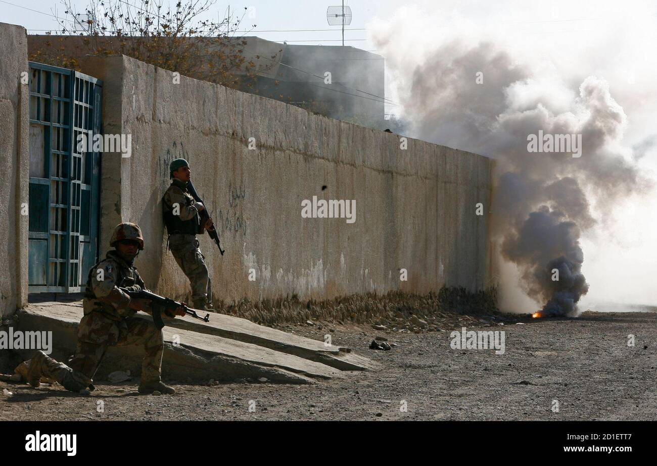 Iraqi soldiers take up position after throwing a smoke grenade during a patrol with troops from the U.S. Army's 101st Airborne Division in Baiji December 27, 2007. REUTERS/Bob Strong (IRAQ) Foto de stock