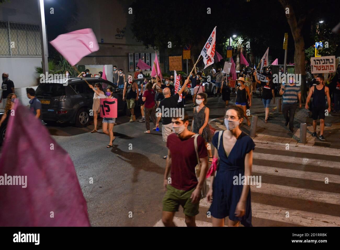 2.10.2020 Tel Aviv, Israel. Protesta contra el primer ministro Netanyahu y el segundo cierre del Coronavirus. Primeras etapas de la protesta en la que cientos marchaban en las calles de Tel Aviv llamando a Bibi Netanyahu a renunciar. Las banderas rosadas simbolizan a las poblaciones debilitadas, la gracia, la empatía se habían convertido en el símbolo de la juventud de lo que ven como la revolución Foto de stock