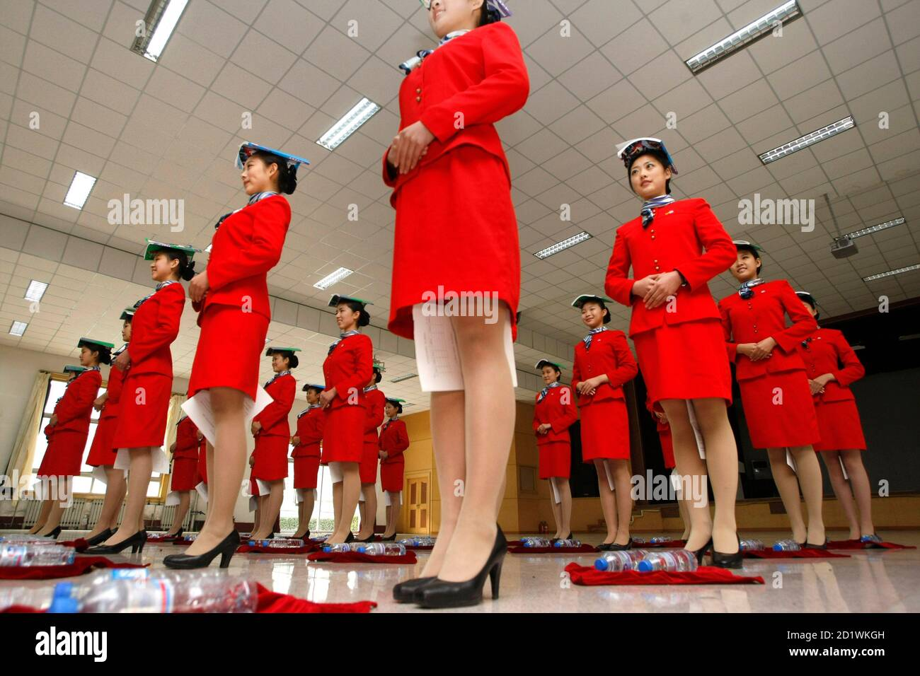Students hold a piece of paper between their legs as they balance a book on their heads during etiquette training at a vocational school in Beijing October 25, 2007. Around 1,400 aviation service students, mostly between the ages of 16 and 17, are currently going through physical conditioning as well as professional training for dressing and etiquette in order to serve as the stewards during the 2008 Beijing Olympics, according to the school announcement.   REUTERS/Jason Lee (CHINA) Foto de stock
