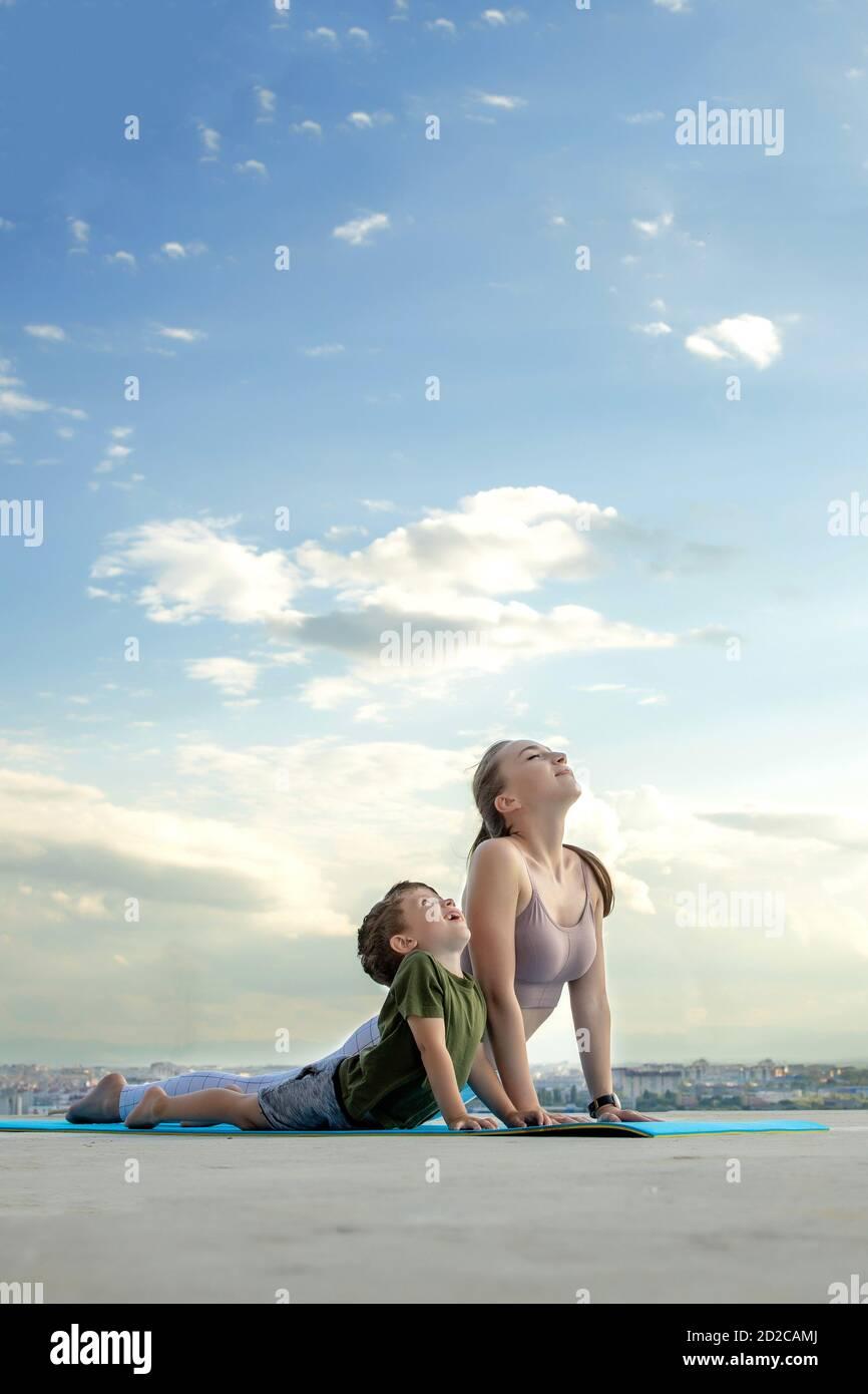 Madre e hijo haciendo ejercicio en el balcón en el fondo de una ciudad durante el amanecer o el atardecer, concepto de un estilo de vida saludable Foto de stock