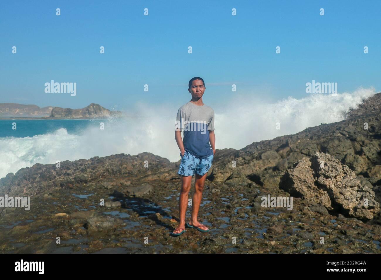 Olas golpeando rocas redondas y salpicando. Un joven está de pie en una orilla rocosa y las olas chocan contra un acantilado Foto de stock