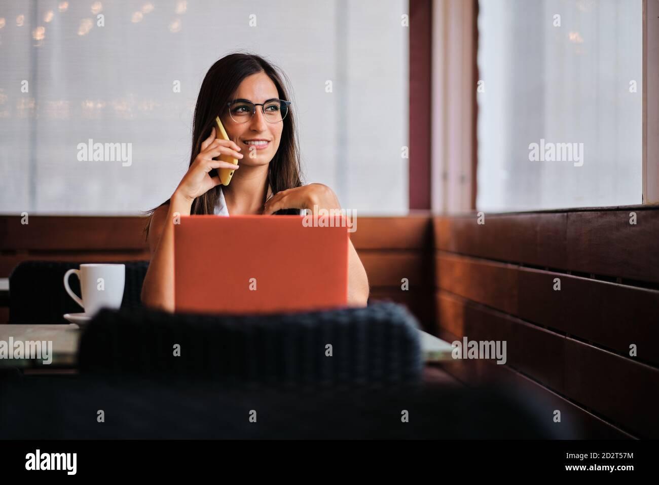 Una empresaria encantada trabajando remotamente en el café mientras discutía negocios problemas con el smartphone y sentarse en la mesa con el ordenador portátil Foto de stock