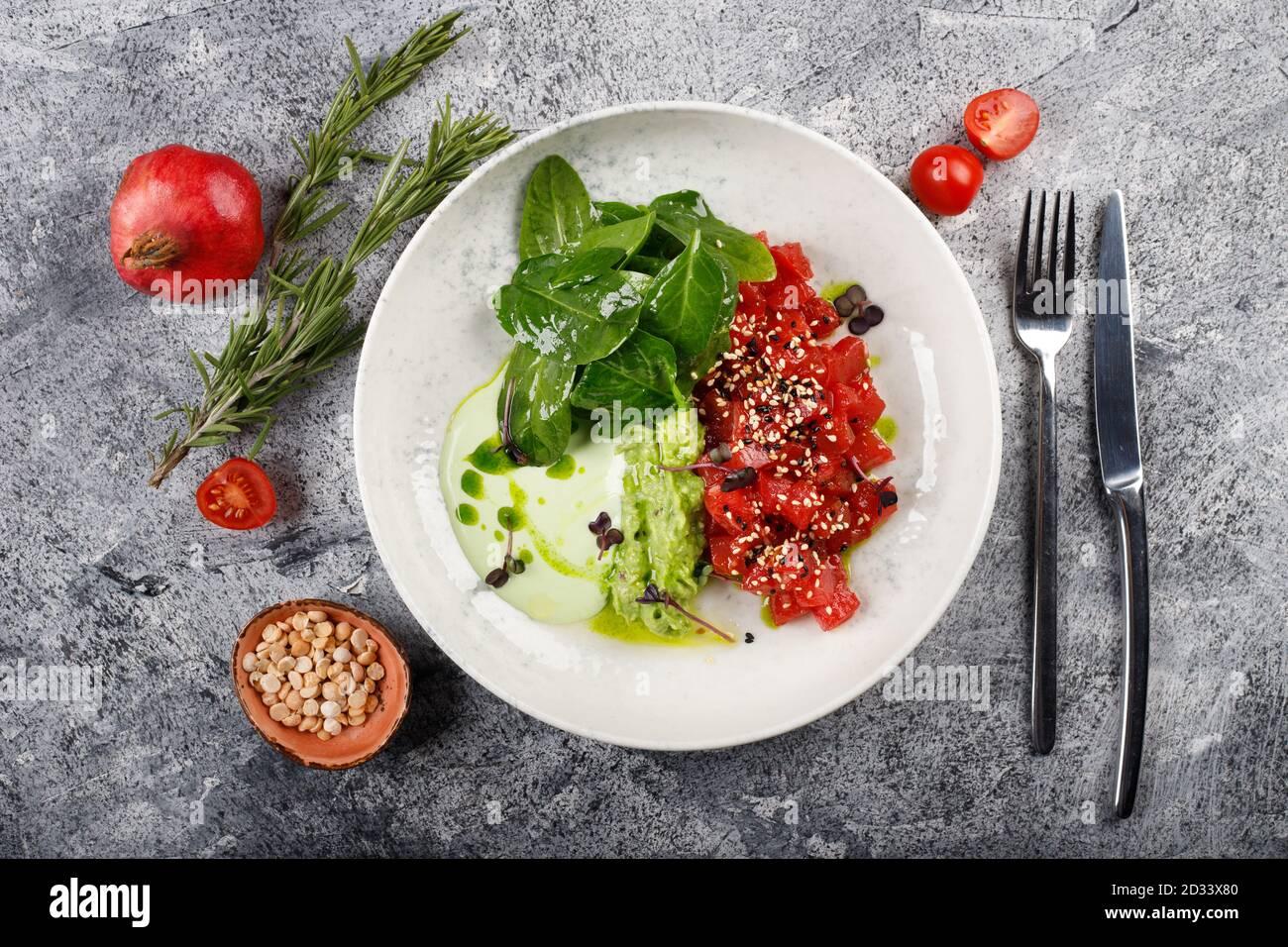 Exquisito pescado tartar filete de atún crudo con verdes de cerca en un plato blanco Foto de stock