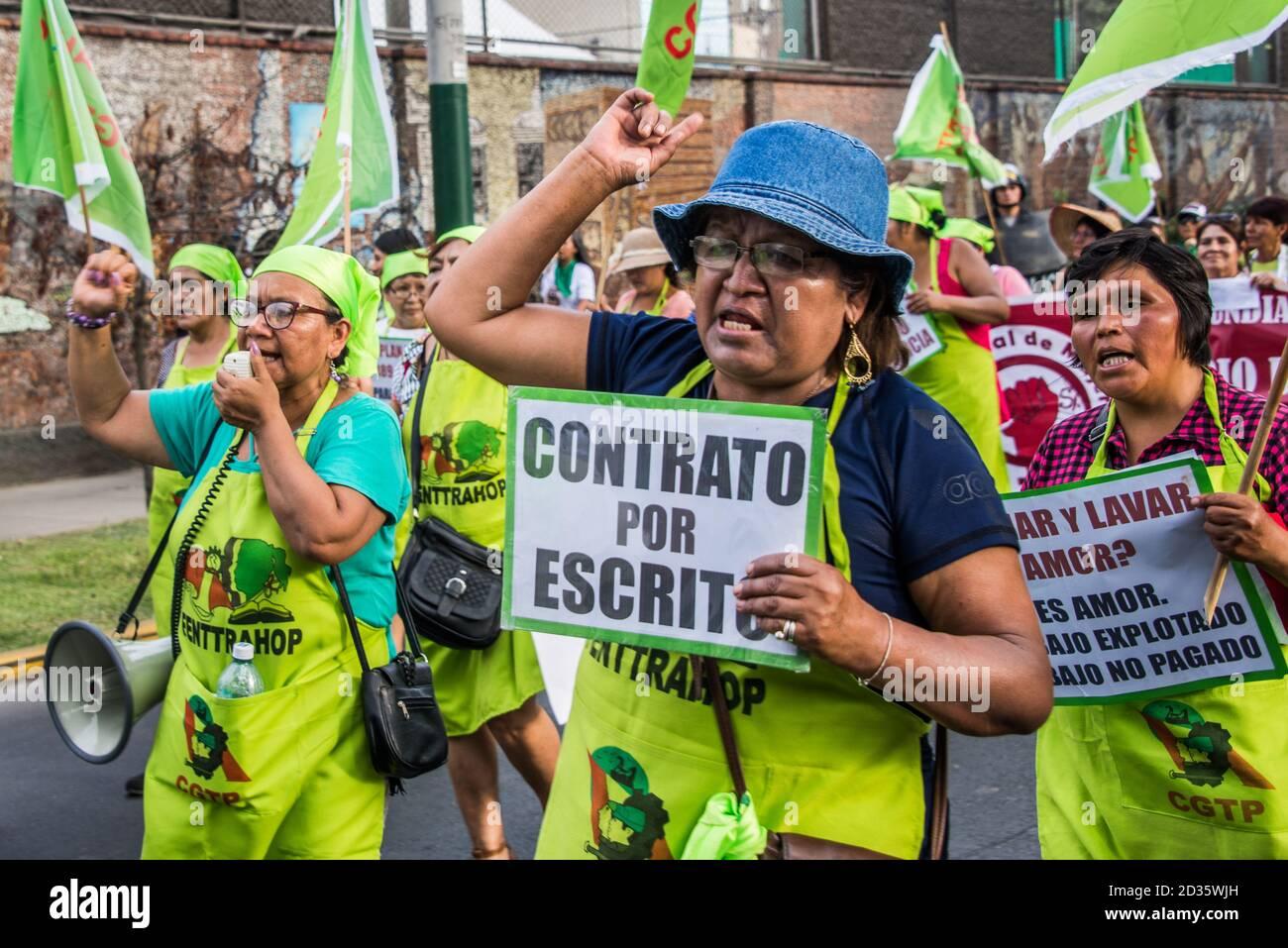 Trabajadoras protestando por la falta de derechos laborales, exigiendo contratos escritos durante la marcha del día Internacional de la Mujer 2020, Lima, Perú Foto de stock