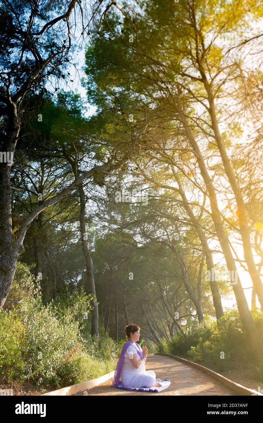La mujer meditando sentada en el loto pose con sus manos delante de su pecho, en anjali mudra, en un camino del bosque al atardecer Foto de stock