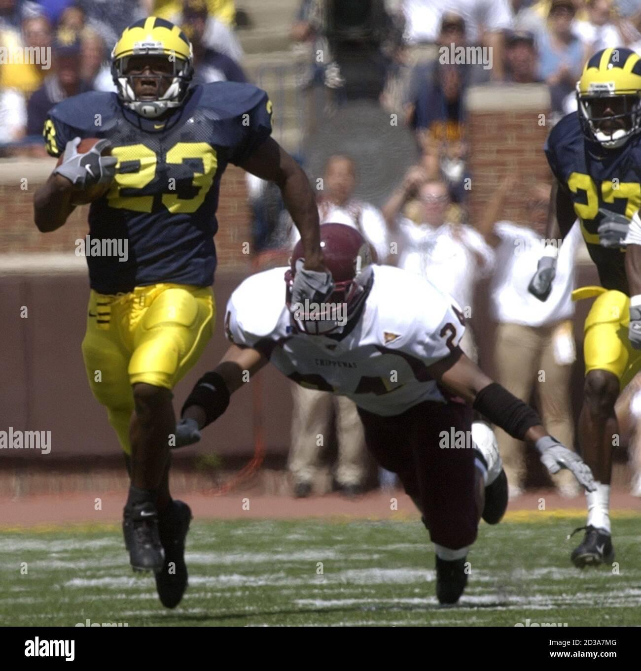 La Universidad de Michigan corriendo atrás Chris Perry (23) lleva la pelota por 33 yardas antes de ser tripped para arriba por el Central Michigan James King (24) en el tercer cuarto del juego en el estadio de Michigan en Ann Arbor, 30 de agosto de 2003. Michigan venció a Central 45-7. REUTERS/Rebecca Cook RC Foto de stock