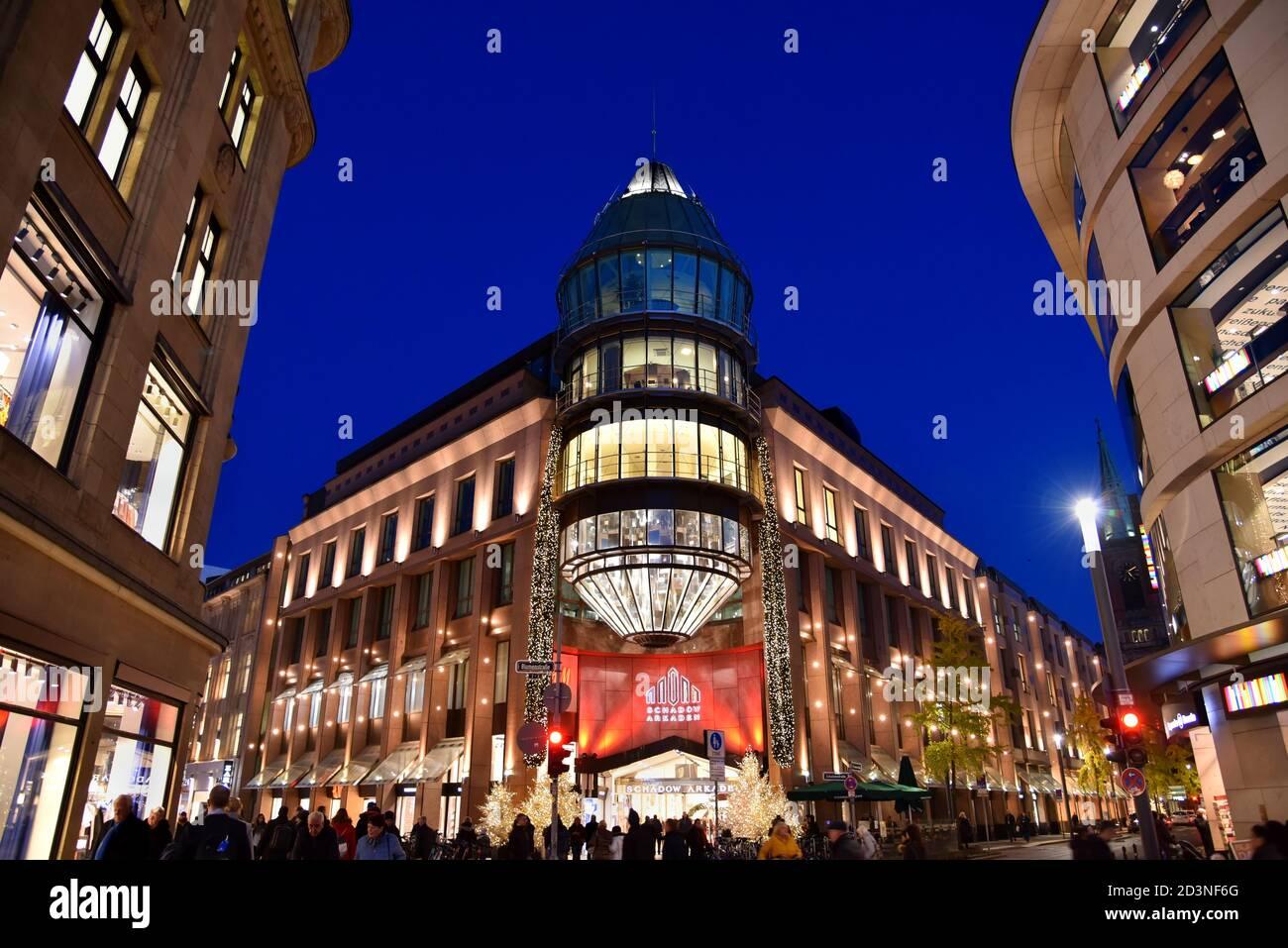 Fachada moderna del centro comercial 'Schadow-Arkaden' en el centro de Düsseldorf con iluminación navideña. Foto de stock