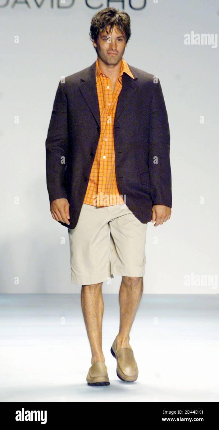 Un Modelo Que Lleva Una Chaqueta Gris Una Camisa Con Estampado Naranja Y Pantalones Caqui Camina