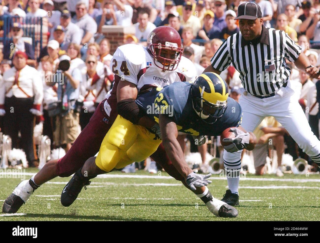 El regreso de la Universidad de Michigan Chris Perry (23) se sumerge en un touchdown con el Central Michigan James King (24) fallando en detenerlo en el segundo cuarto del juego en el Michigan Stadium en Ann Arbor, 30 de agosto de 2003. REUTERS/Rebecca Cook RC Foto de stock