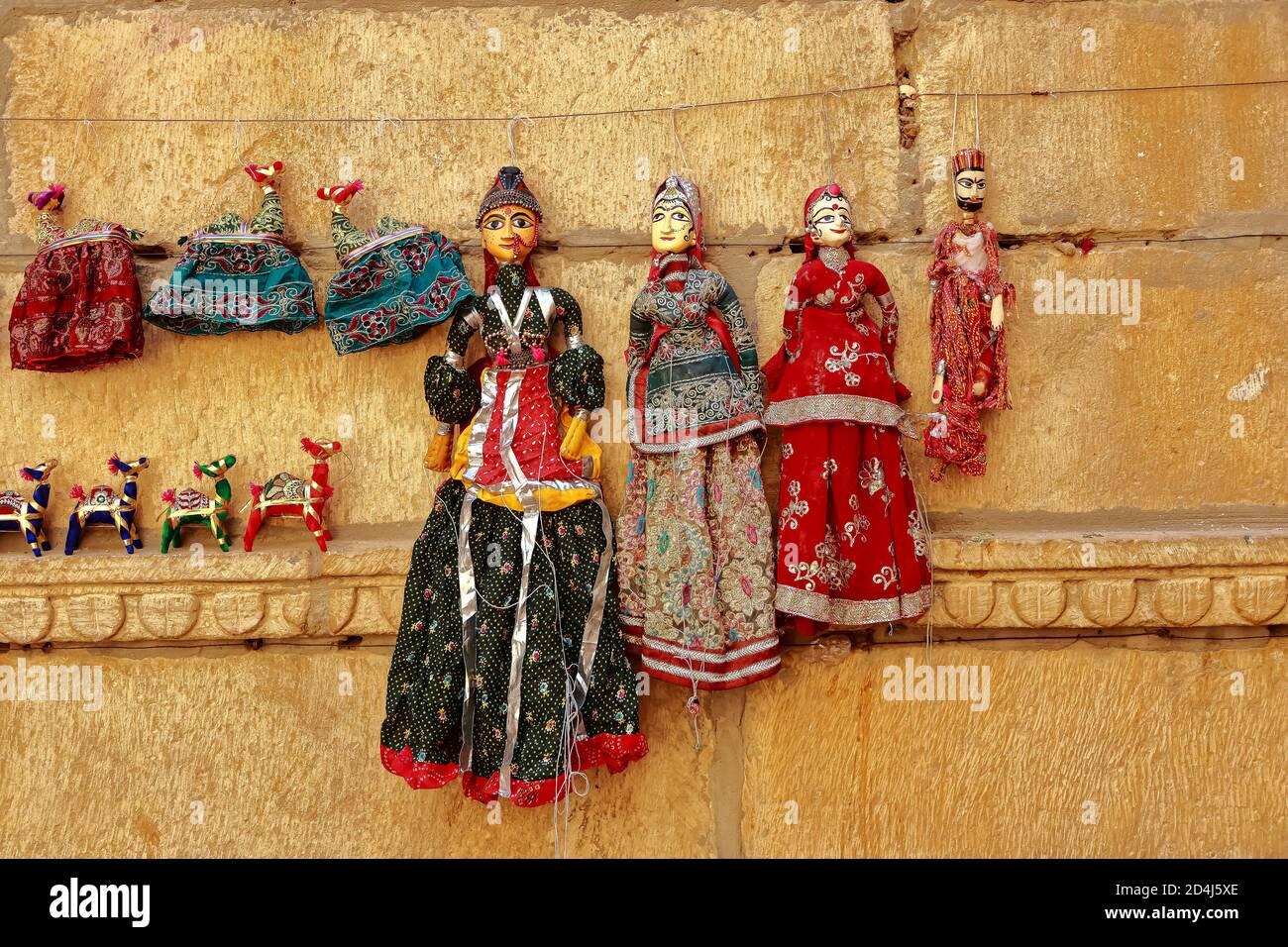 Marionetas coloridas con forma humana con ropa de colores colgando contra el Muro en Rajasthan India el 21 de febrero de 2018 Foto de stock