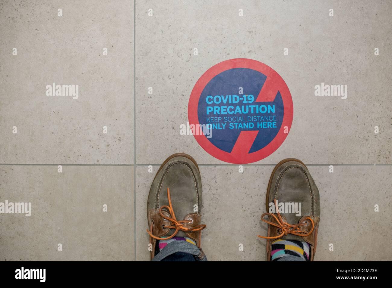 Señal de distancia social en el suelo con zapatos de pie al lado él Foto de stock