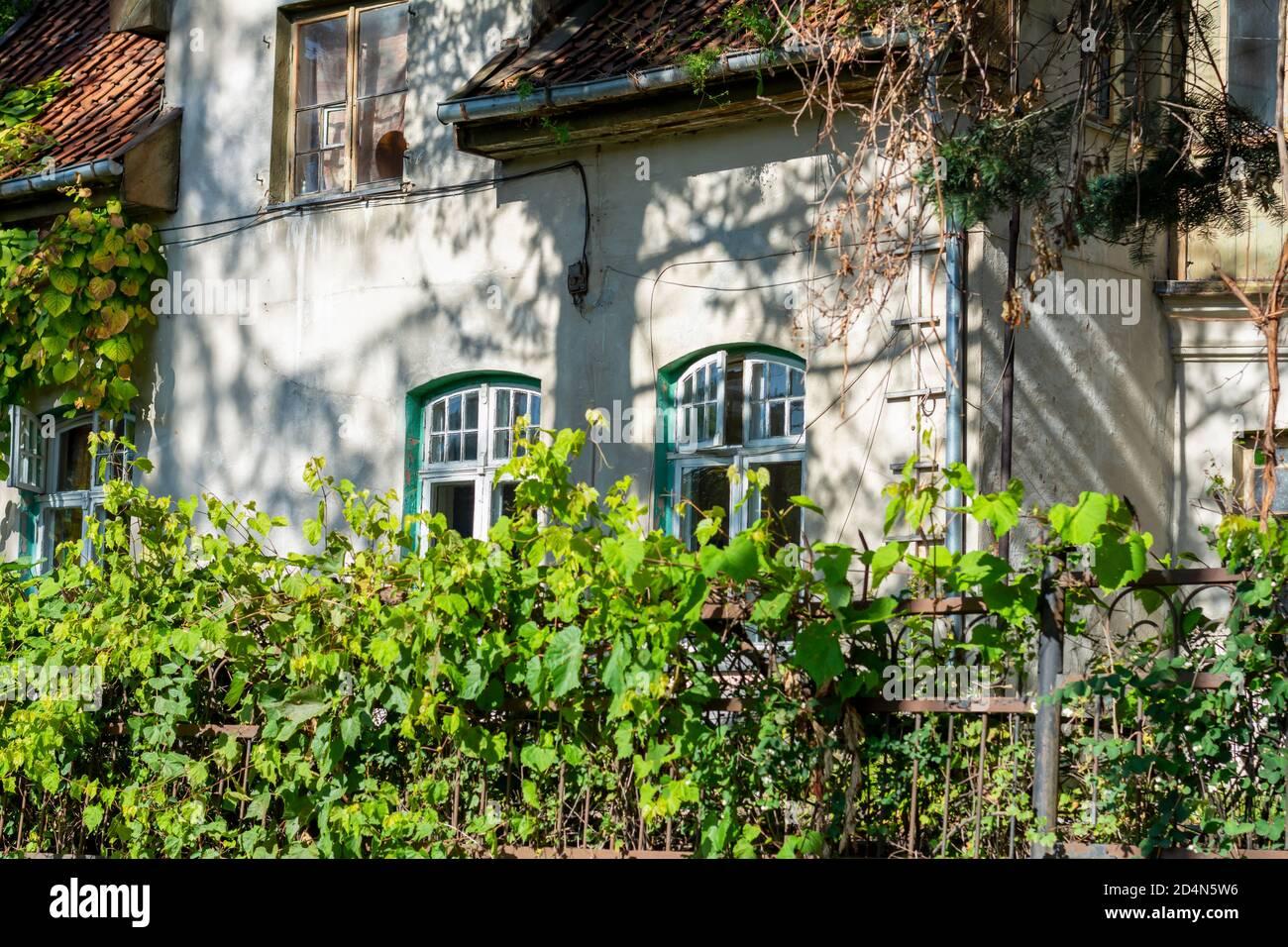 Fachada de una antigua casa con ventanas y azulejos de madera. casa del siglo 19 sin restauración. Foto de stock
