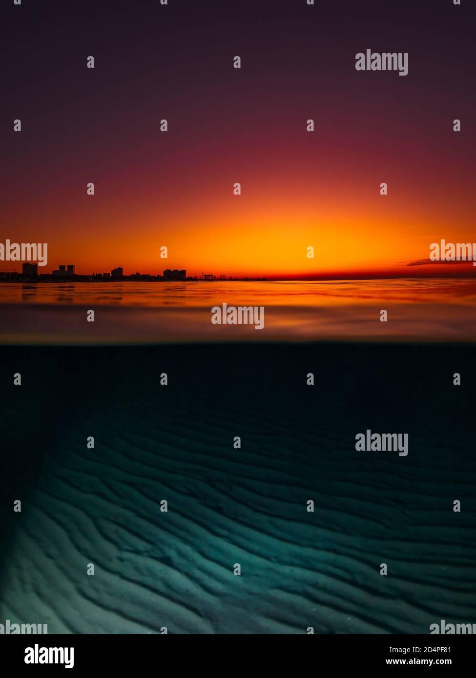 Vista dividida con puesta de sol brillante y fondo de mar de arena bajo el agua. Foto de stock