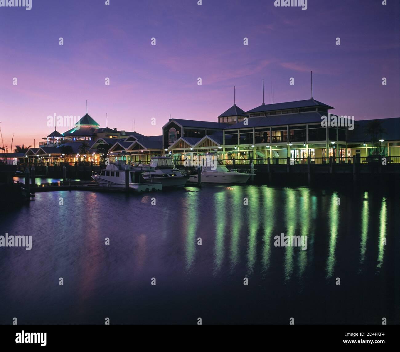 Australia. Queensland. Región de Cairns. Puerto Douglas. Puerto de barcos Marina Mirage y galería comercial al atardecer. Foto de stock