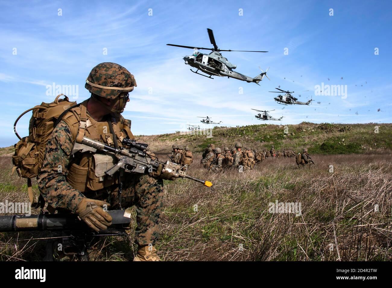 Los Marines de Estados Unidos con el Segundo Batallón, 4º Regimiento de la Infantería de Marina, la primera división de infantería de marina proporcionan seguridad para UH-1y venenos con Luz Marina 469 escuadrón de helicópteros de ataque, aviones marinos Grupo 39, 3º Marine de alas de avión, en una zona de aterrizaje durante el ejercicio veneno tormenta en la isla de San Clemente, California, el 15 de enero de 2020. Ejercicio veneno Storm demuestra la versatilidad del veneno letal en el suministro de opciones, ya sea que operen desde el mar o tierra. Es la capacidad para desplegar rápidamente desde el buque-costa, apoyar las fuerzas de tierra con su propio fuego de apoyo orgánico y estar armados y repostado en emplazamientos temporales es inigualable. El Foto de stock