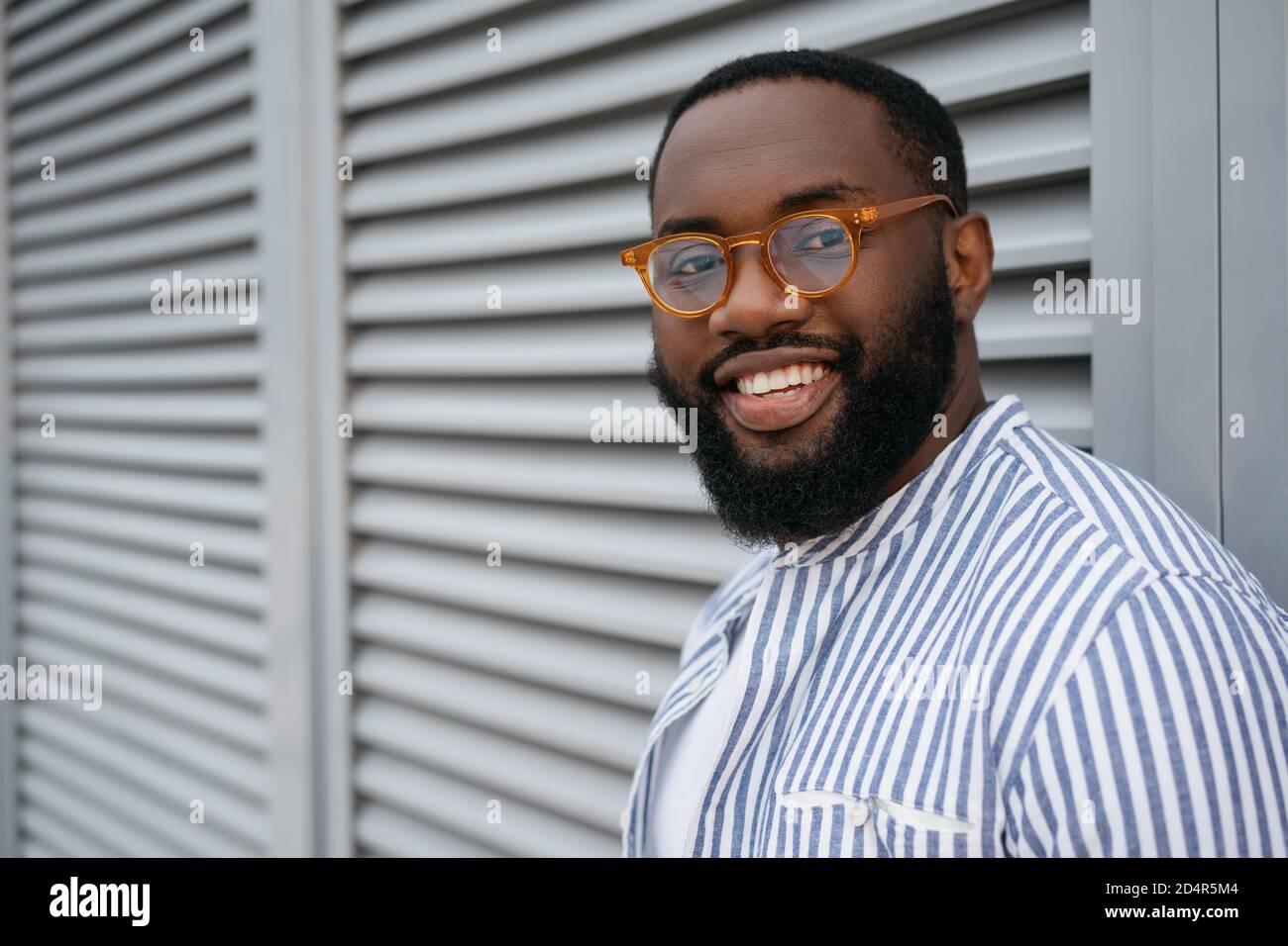 Primer retrato de un hombre afroamericano con éxito que llevaba gafas con estilo. Modelo guapo mirando la cámara, sonriendo, aislado en el fondo Foto de stock