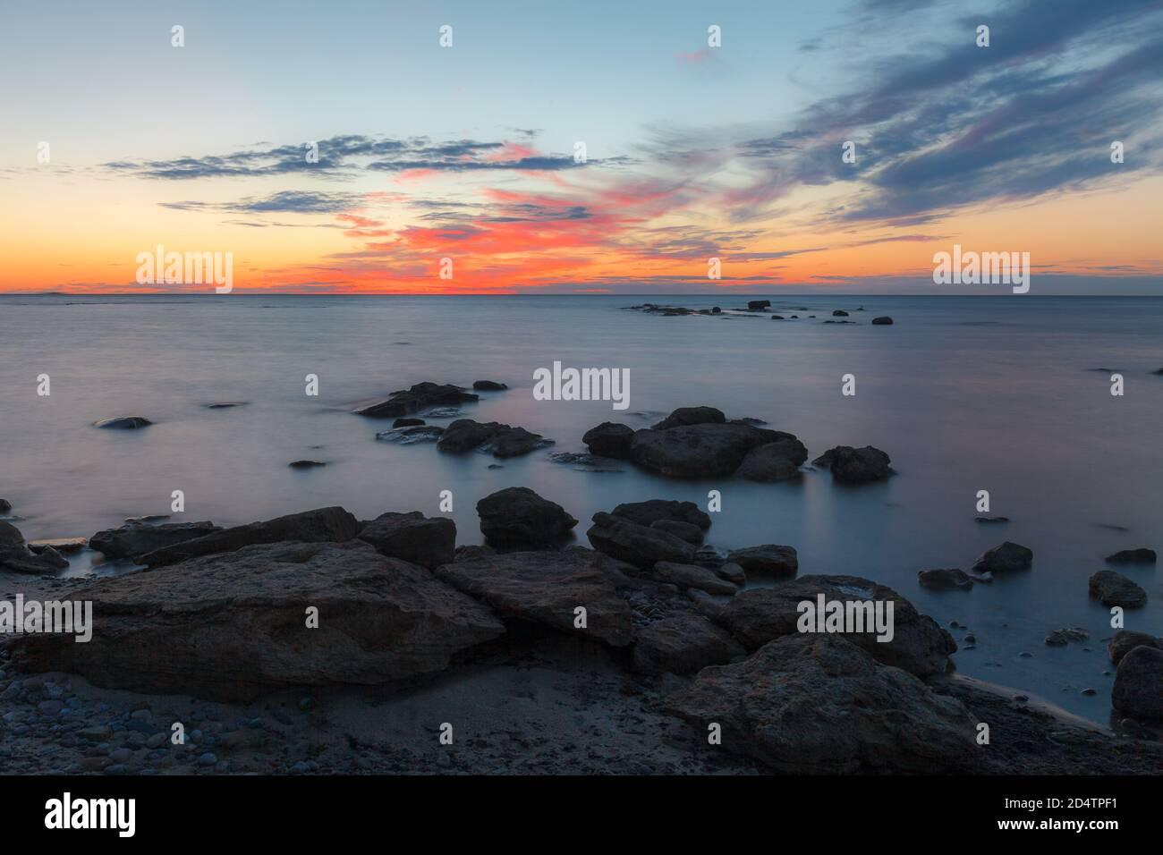 Puesta de sol al atardecer sobre la costa rocosa del mar Báltico. Cielo casi despejado y correa naranja a lo largo del horison. Estonia. Foto de stock