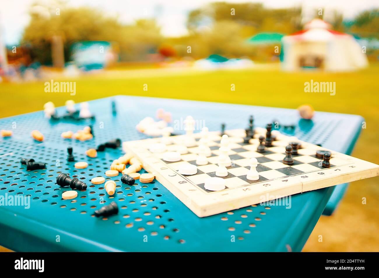 Ajedrez y damas están esparcidos en la mesa del parque. Un juego intelectual para desarrollar estrategias y tácticas. Pasatiempo útil en la calle. Entretenimiento en el complejo. Tablero de ajedrez y piezas en la mesa. Foto de stock