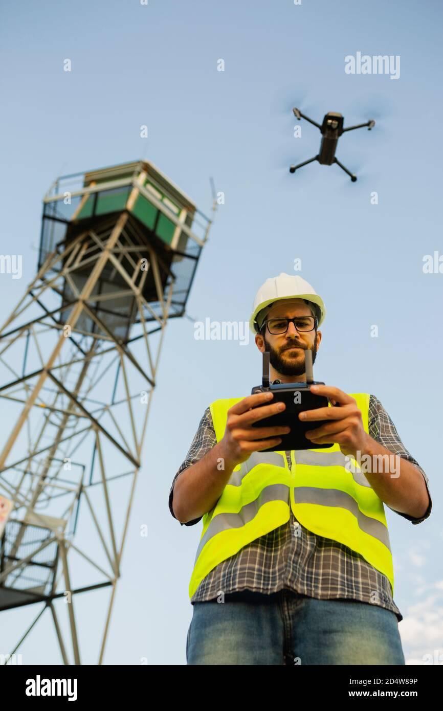 Un operario de aviones teledirigidos piloteando un avión junto a una torre Foto de stock
