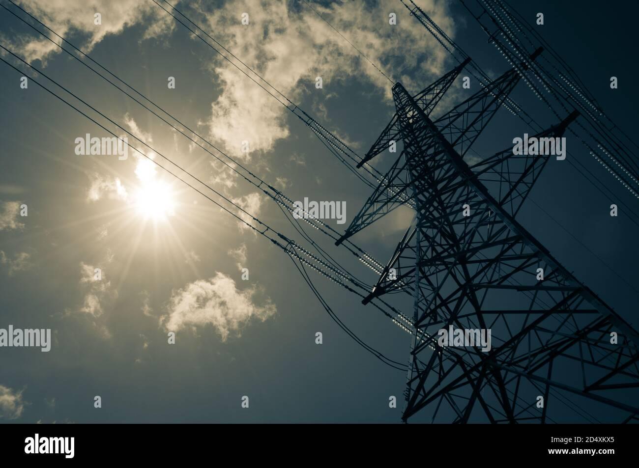 Un pilón de electricidad se alza alto en el calor del sol de verano con unas pocas nubes wispy. Concepto de energía solar. Foto de stock