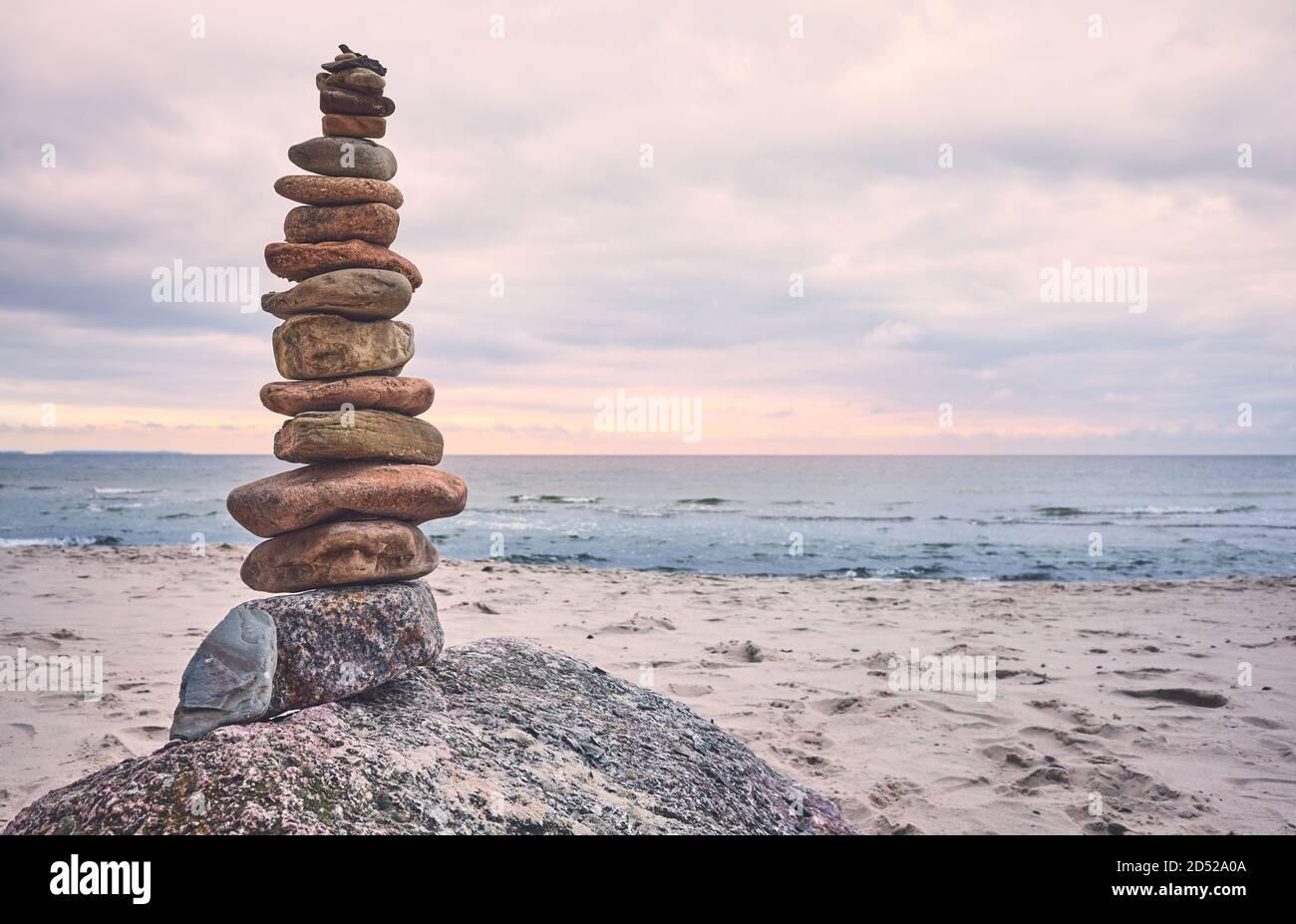 Pirámide de piedra en una playa, zen, concepto de armonía y equilibrio, tono de color aplicado. Foto de stock