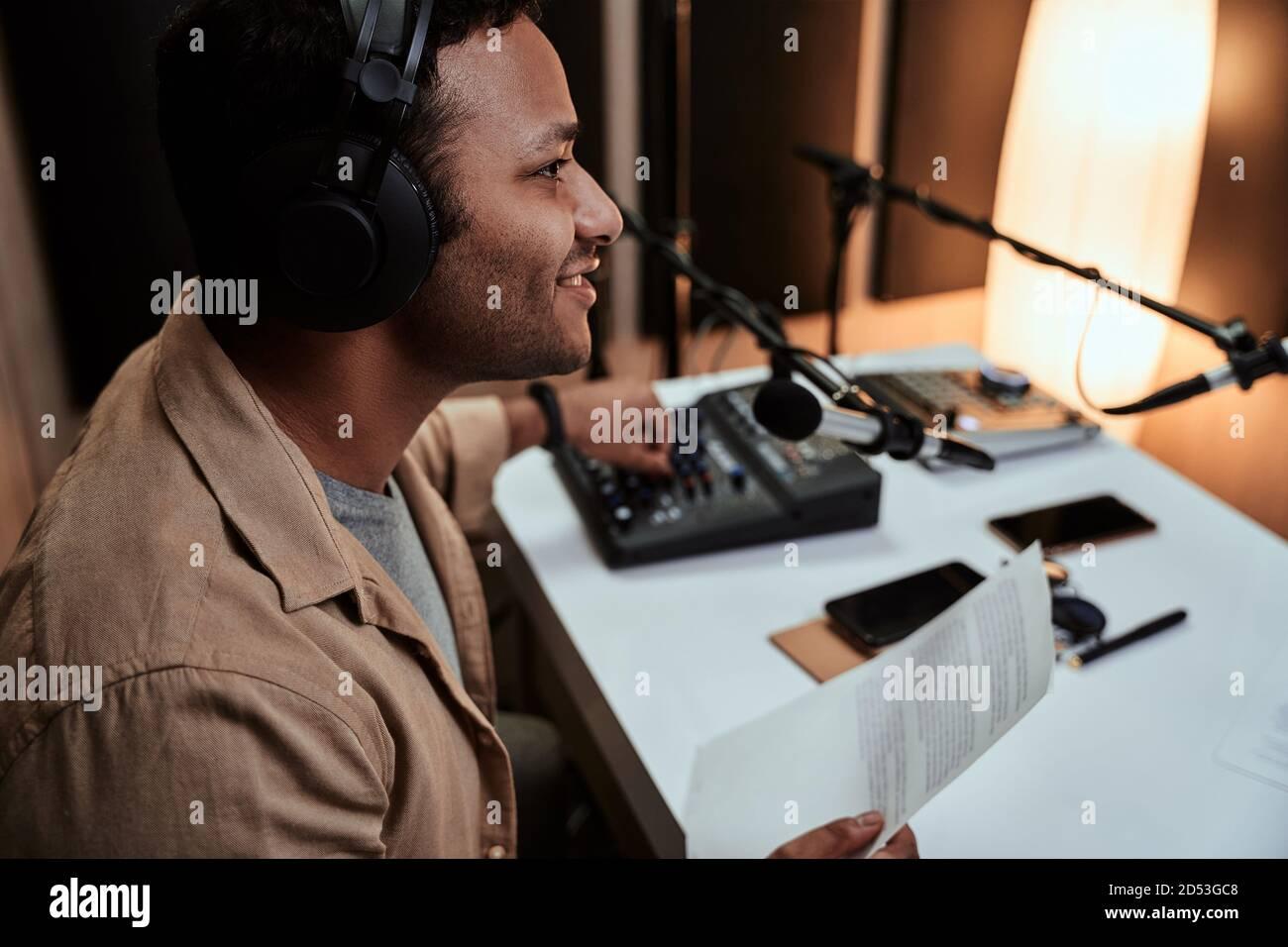 Retrato de un joven presentador de radio masculino en vivo en el aire, hablando en micrófono, sosteniendo un papel de guión mientras estaba sentado en el estudio Foto de stock