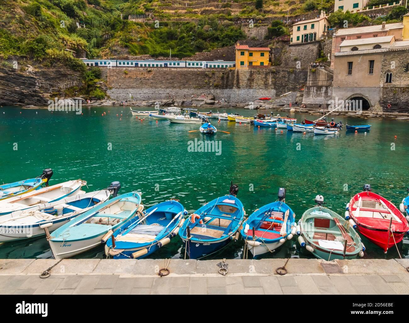 Preciosas vistas del puerto de Vernazza en la zona costera de Cinque Terre. Pequeños barcos, flotando en aguas poco profundas de color turquesa, están atados al muelle y en... Foto de stock