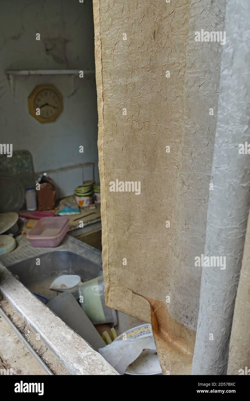 Cortina sucia y fregadero de la cocina con platos sin lavar en casa abandonada. Foto de stock