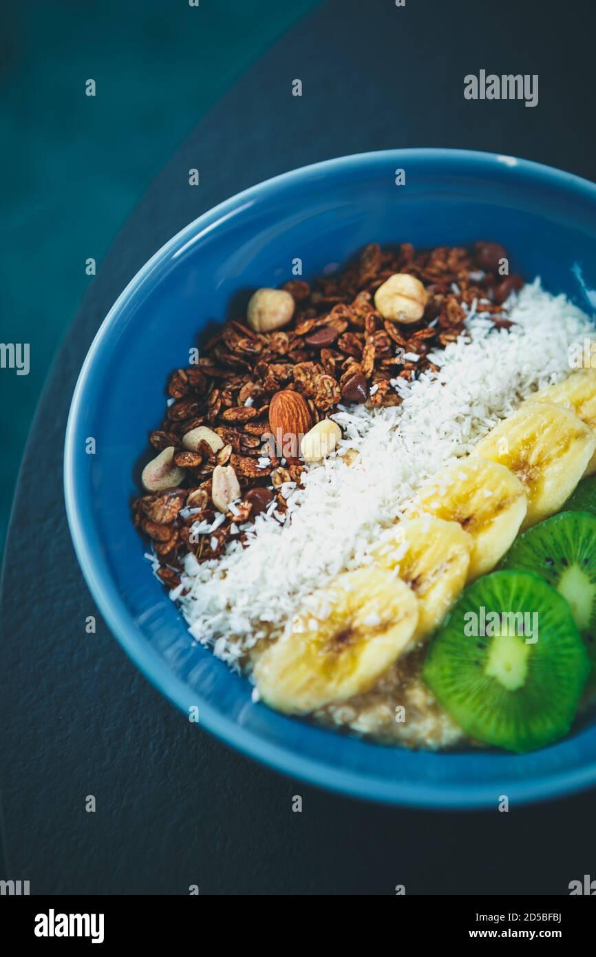 Deliciosa comida vegetariana en un plato de cerámica azul Mesa en vegan cafe.ingredientes frescos de comida natural preparados para el desayuno.hervidos blanco Foto de stock