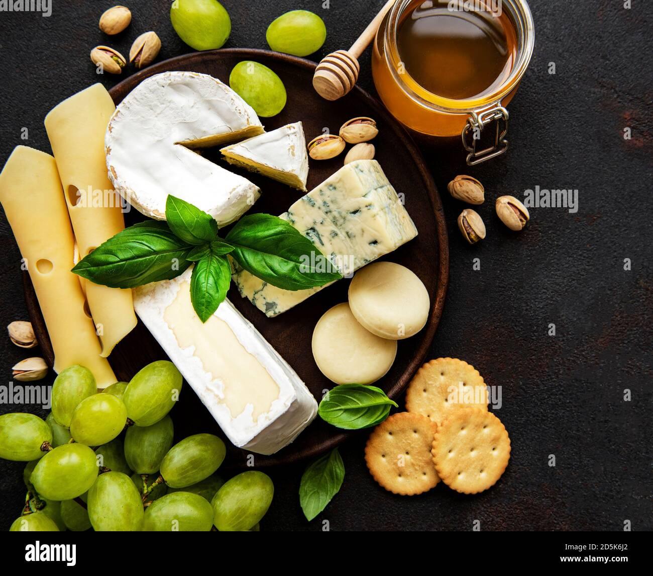 Varios tipos de queso sobre un fondo de concreto negro Foto de stock