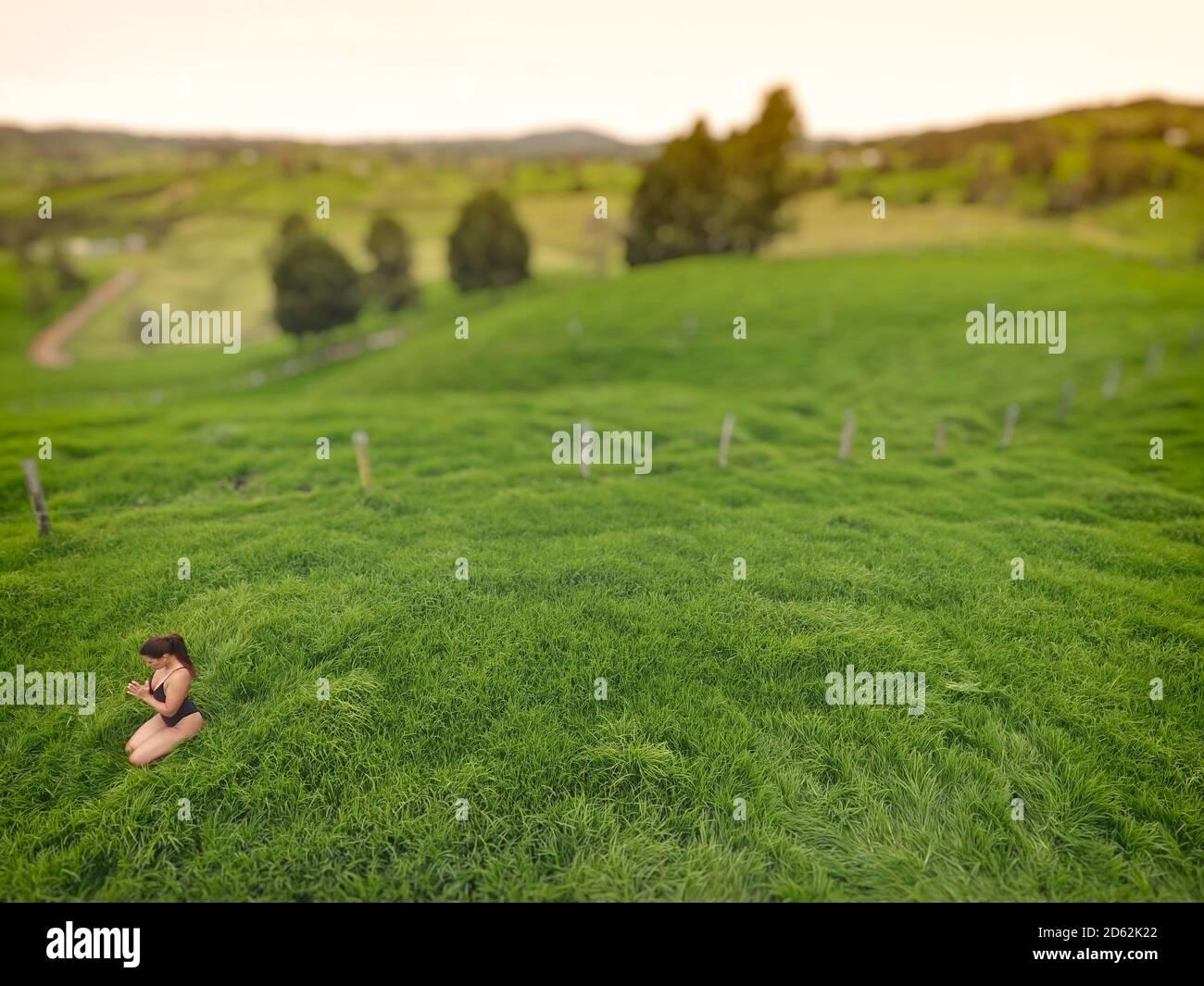 Mujer meditando en un campo de hierba vacío. Foto de stock