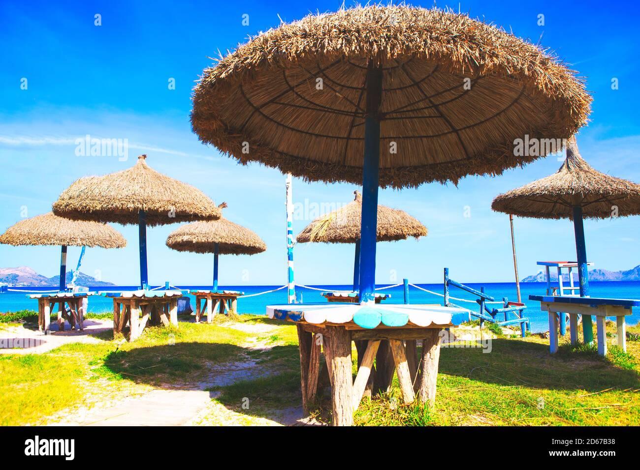 Sombrillas y mesas de playa exóticas. Terraza tropical de verano Foto de stock