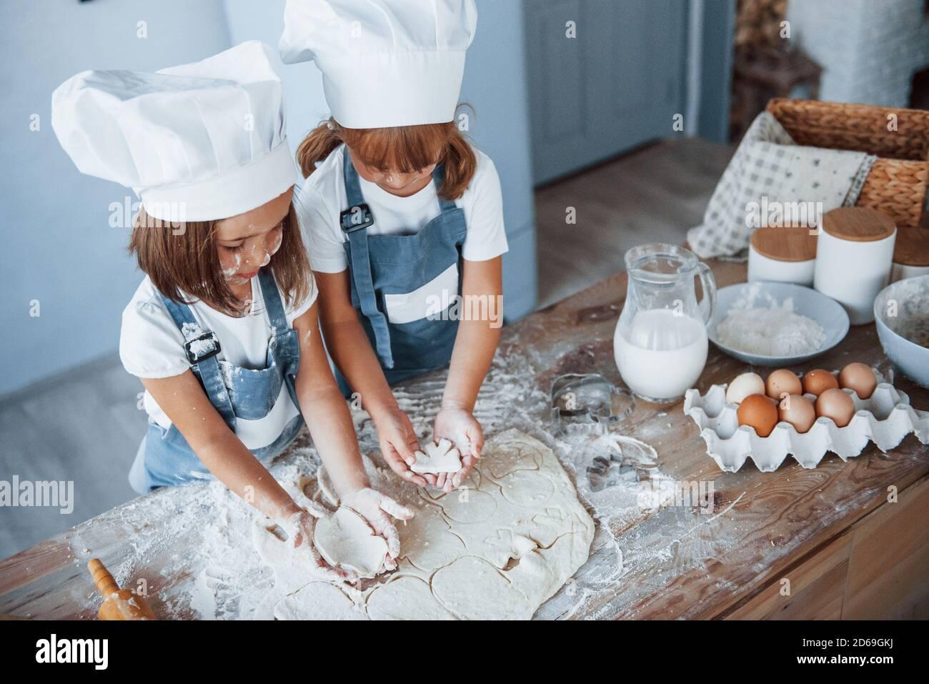 Concentrarse en cocinar. Los niños de la familia en el uniforme blanco del chef preparando la comida en la cocina Foto de stock