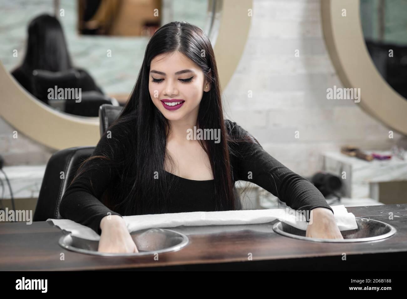 Niña India bastante joven sentada en un salón de manicura, concepto de salón de belleza, concepto de belleza y cuidado de la salud. Foto de stock