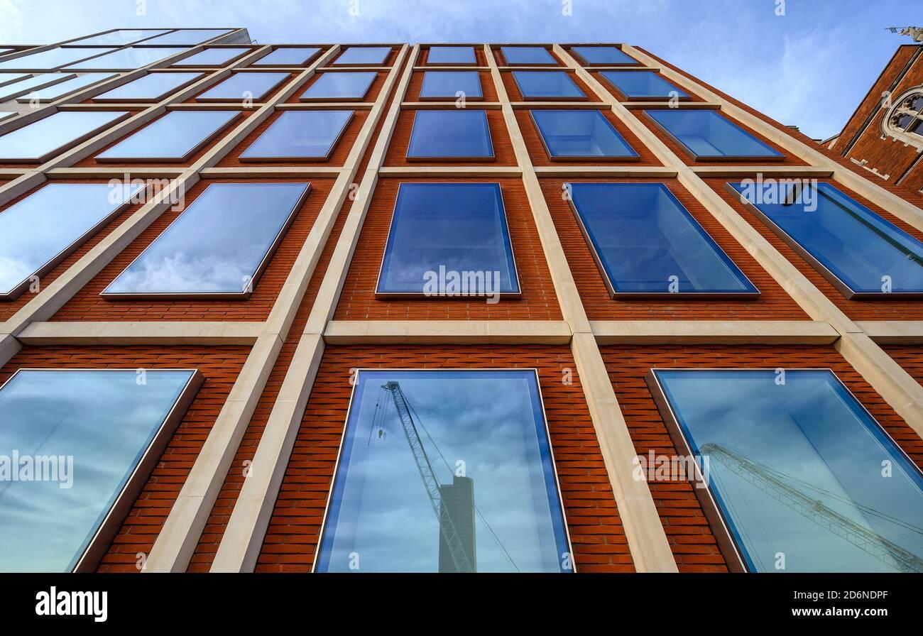 Un edificio de oficinas en Londres con ladrillos rojos y ventanas azules. Las líneas rectas dan una fuerte perspectiva hacia arriba. Reflejos de grúas en las ventanas. Foto de stock