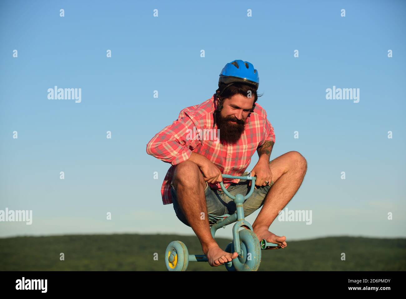 Hombre divertido en una bicicleta para niños. Paseo en bicicleta nerdy. Foto de stock