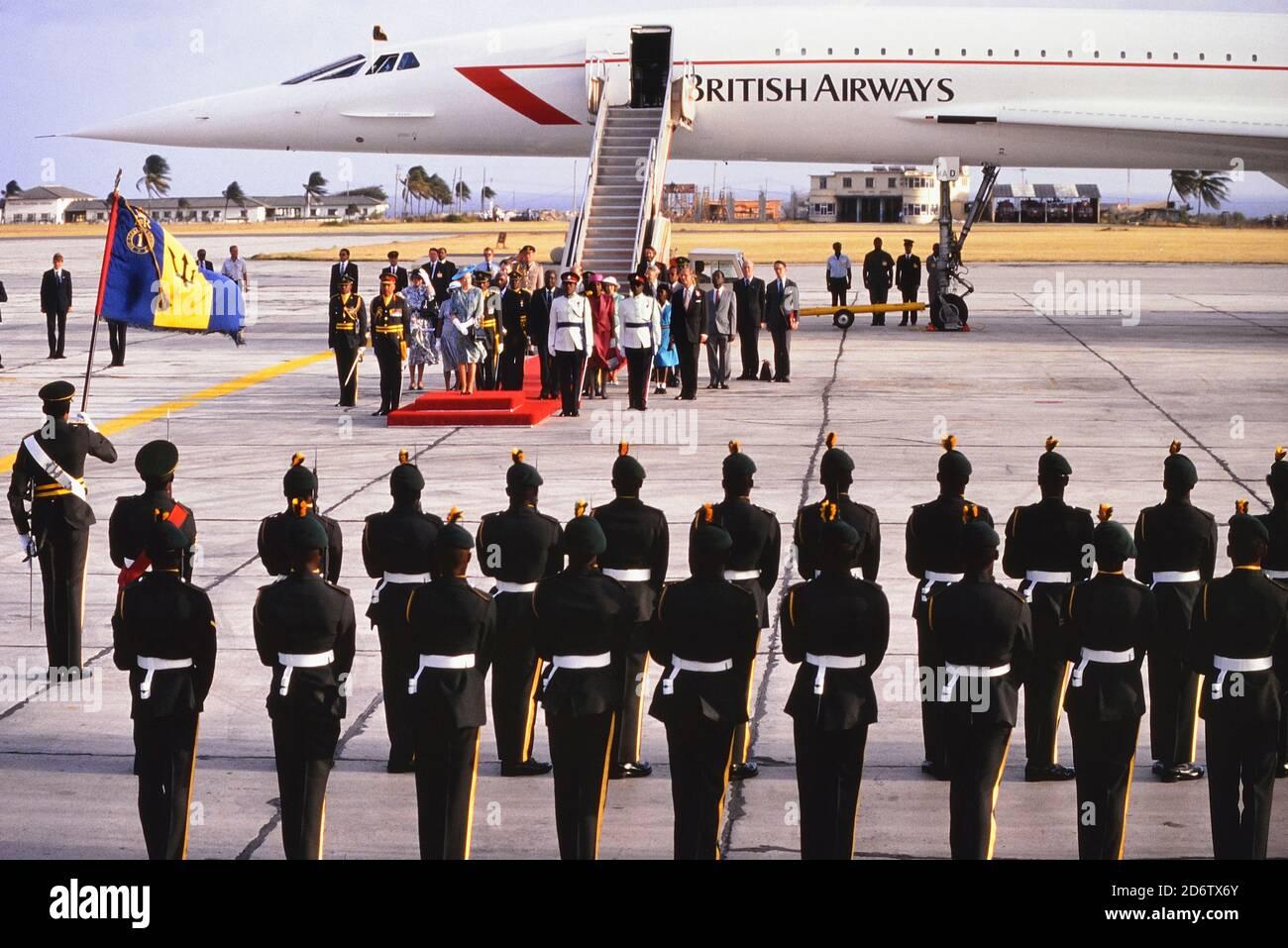 Reina Isabel II de Gran Bretaña de pie sobre la alfombra roja durante una ceremonia de bienvenida después de aterrizar en el Aeropuerto Internacional Grantley Adams en un vuelo de B.A. Concorde al comienzo de su visita de cuatro días a la Isla del Caribe de Barbados. 8 de marzo de 1989. Foto de stock
