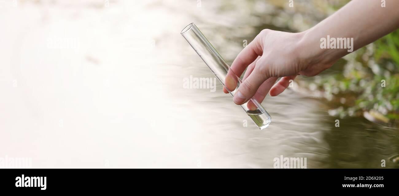 Una muestra de agua del río. Consumo de agua. Abstracción de agua. Banner agua de muestra. El concepto de un ambiente limpio. Foto de stock