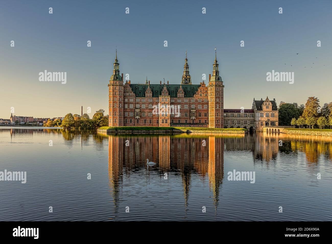 El Castillo Real Frederiksborg brilla bajo el sol y se refleja en el lago con un cisne de natación, Hillerod, Dinamarca, 17 de octubre de 2020 Foto de stock