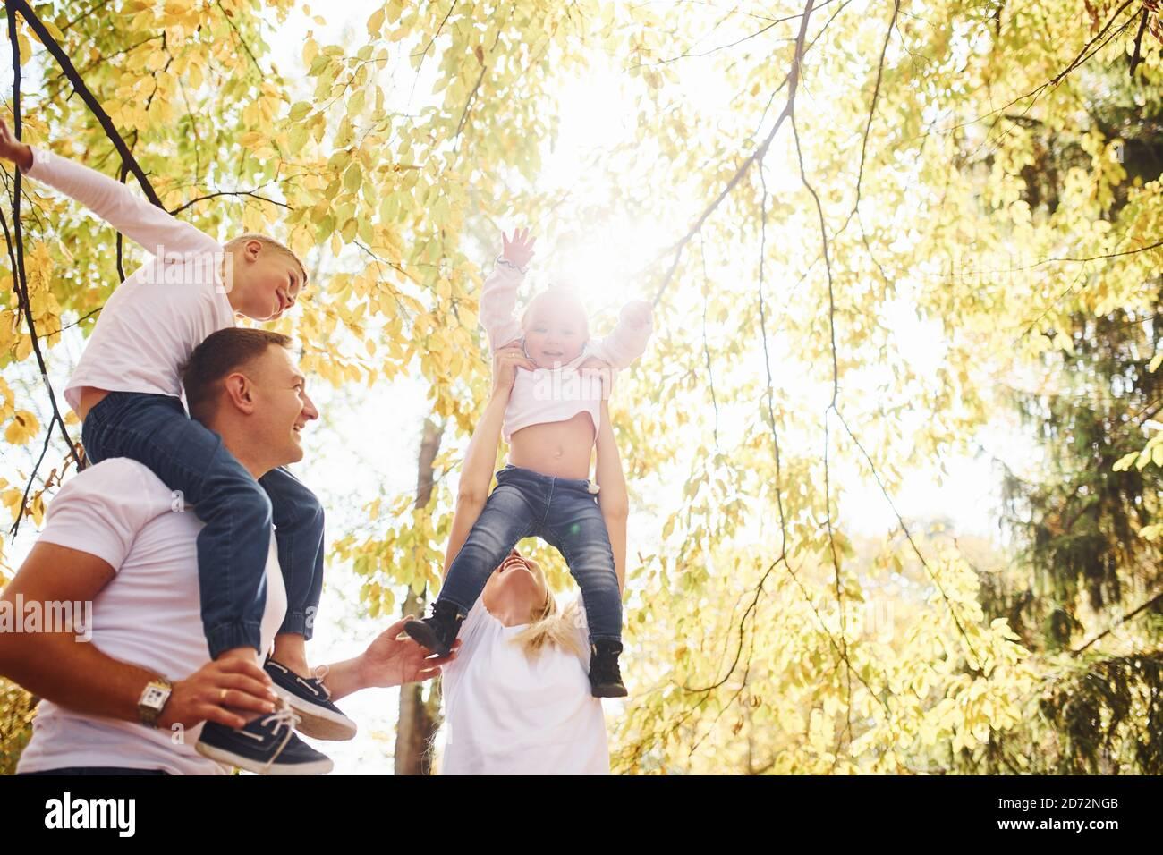 La madre y el papá mantienen a los niños en los hombros y en las manos. Alegre familia joven tienen un paseo juntos en un parque de otoño Foto de stock