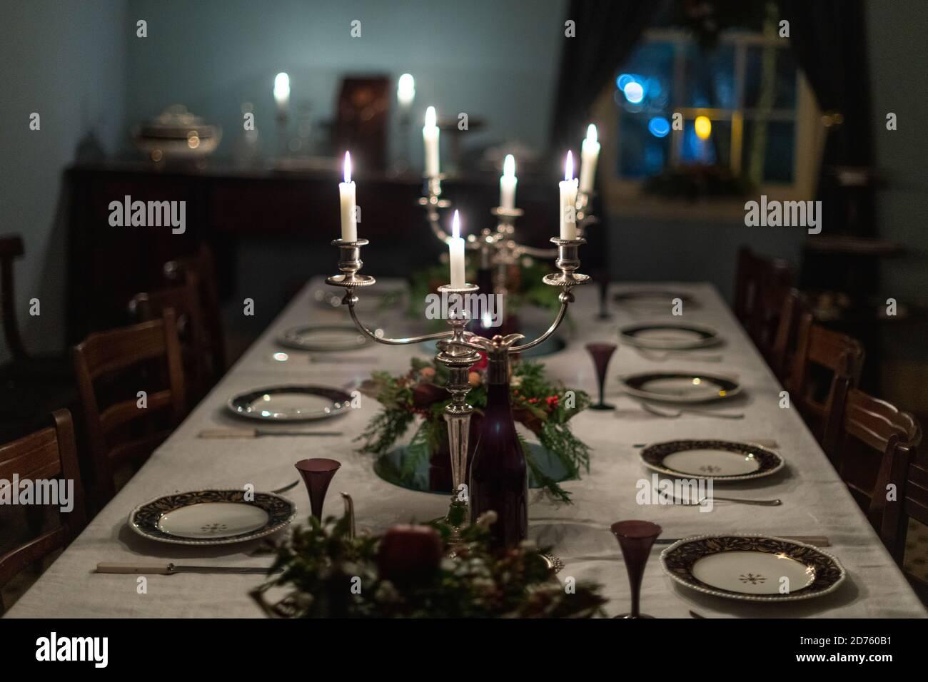 Una mesa de comedor formal romántico y oscuro con platos de porcelana vintage, candelabros de plata con velas encendidas blancas, un mantel blanco, floral Foto de stock
