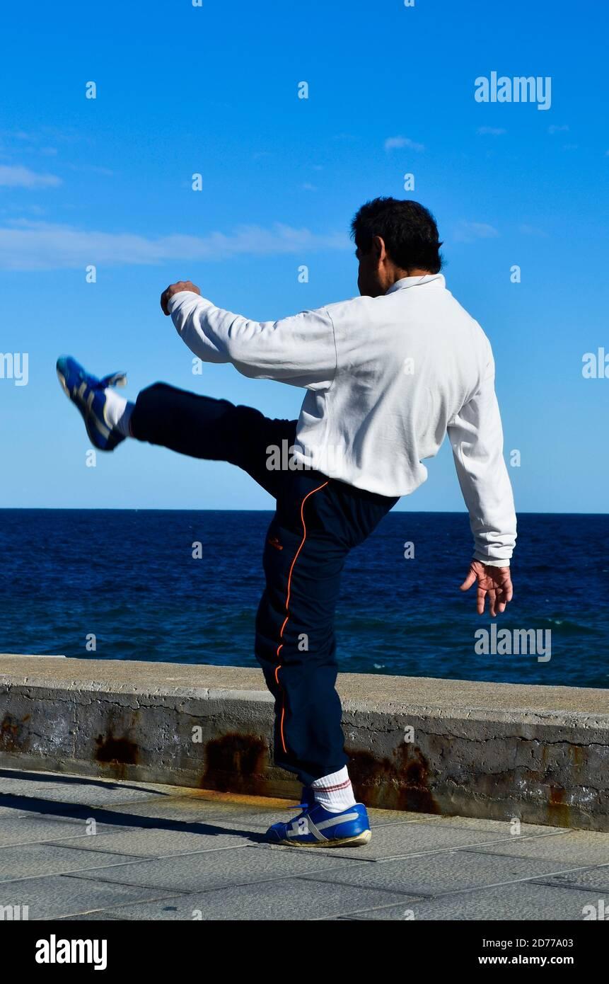Hombre calentándose y estirando las piernas en el muelle. Foto de stock