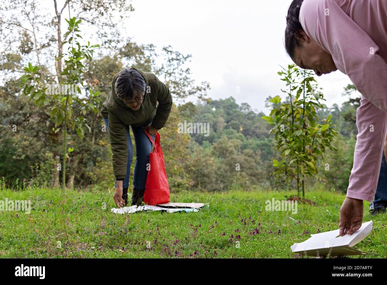 un par de mujeres recogiendo basura de un bosque y.. poniéndolo en una bolsa de tela Foto de stock
