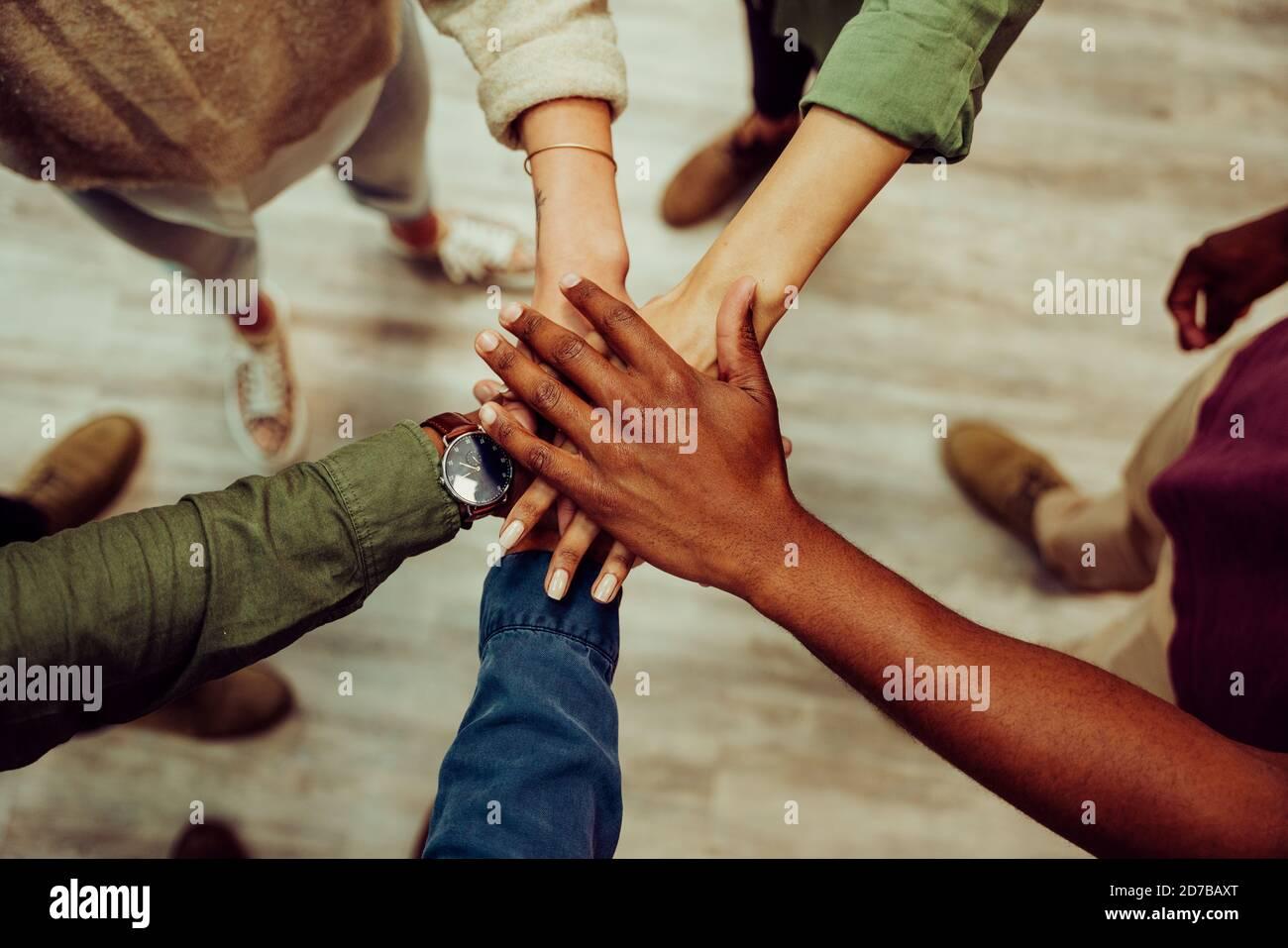 El grupo de negocios exitoso se apila juntos mostrando unidad y trabajo en equipo. Foto de stock