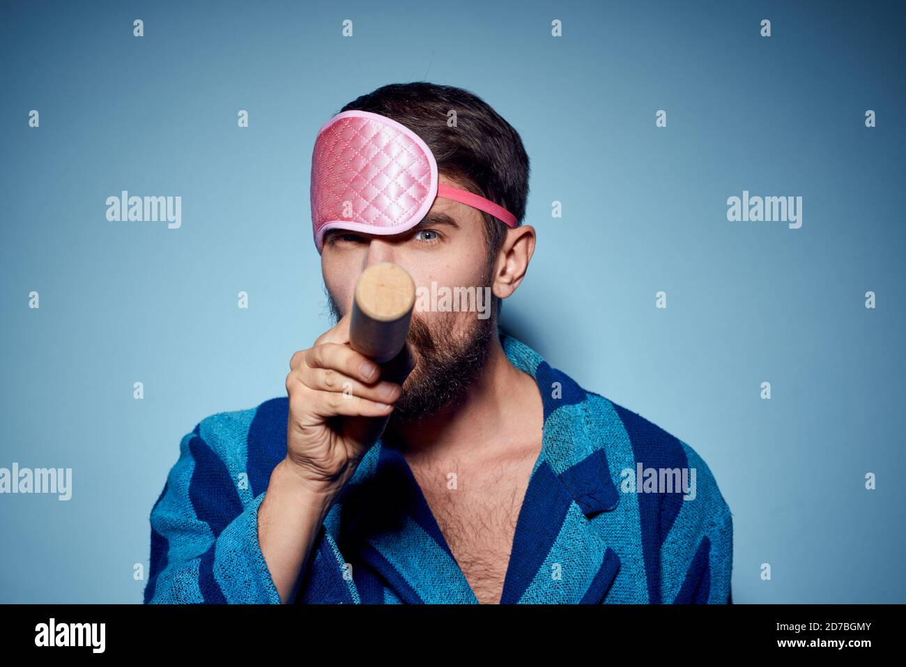 hombre con rodillo y en azul máscara de sueño rosa modelo de emoción de la vista recortada de la túnica Foto de stock